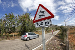 汽车追上一条路的一个骑自行车者有许多曲线的 免版税库存照片