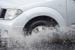 汽车通过一个大水坑飞溅在一条被充斥的街道 免版税库存图片