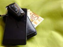 汽车钥匙、钱包和智能手机在绿色纺织品背景 图库摄影