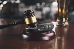 汽车钥匙和啤酒酒精饮料在一块玻璃在一张棕色木桌上 不要喝 库存图片