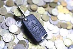 汽车钥匙和硬币在背景 免版税库存图片