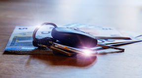 汽车钥匙在欧洲钞票和木桌放置 库存图片
