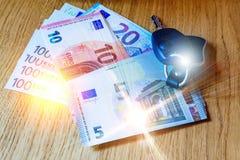 汽车钥匙在欧洲钞票和木桌放置 免版税库存图片