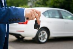 汽车钥匙在白色自动背景的手上 免版税库存照片