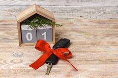 汽车钥匙特写镜头视图与红色弓作为礼物和日历的在木背景的木背景 免版税库存照片