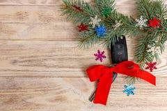 汽车钥匙特写镜头视图与红色弓的作为在木背景的礼物 免版税库存照片