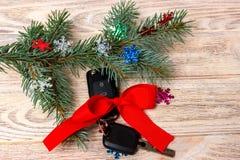 汽车钥匙特写镜头视图与红色弓的作为在木背景的礼物 库存照片