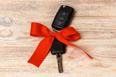 汽车钥匙特写镜头视图与红色弓的作为在木背景的礼物 库存图片