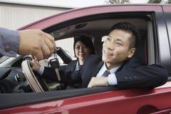 给汽车钥匙的技工愉快的夫妇 库存图片