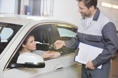 给汽车钥匙的汽车修理工女性顾客在车间 库存图片