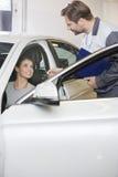 给汽车钥匙的汽车修理工维修车间的女性顾客 图库摄影