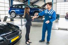 给汽车钥匙的男性技工客户在为服务以后 库存照片