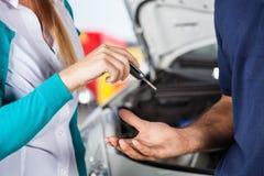 给汽车钥匙的顾客技工 免版税库存图片