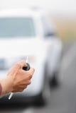汽车钥匙-供以人员锁按在新的汽车的汽车键 免版税库存图片