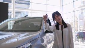 汽车销售中心,专业手钥匙的汽车卖主亚洲女性举行画象的新的汽车待售 影视素材