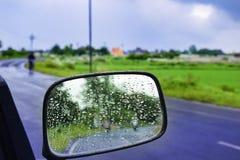 汽车镜子立即使用的玻璃窗-移动与自然水的结露滴下 抽象照片 免版税图库摄影
