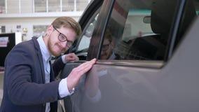 汽车陈列室,愉快的采购员人眼镜高兴地抚摸新的机器的轻轻地微笑在汽车销售中心 股票录像