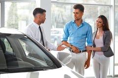 汽车陈列室 买一辆新的汽车的年轻夫妇在经销权 库存照片