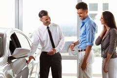 汽车陈列室 买一辆新的汽车的年轻夫妇在经销权 免版税库存图片