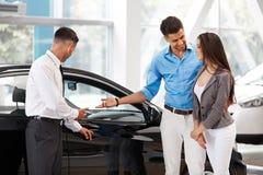 汽车陈列室 买一辆新的汽车的年轻夫妇在经销权 图库摄影