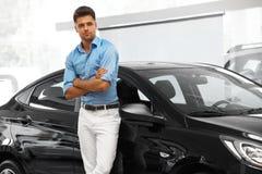 汽车陈列室 在他的梦想附近汽车的愉快的人  免版税库存照片