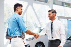 汽车陈列室 年轻夫妇会见自动沙龙的卖主 免版税库存图片