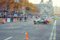 汽车障碍滑雪和漂泊竞争在市中心,在路的汽车有锥体的 免版税库存图片
