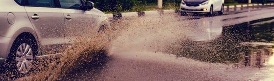 汽车飞溅水定调子的雨水坑 免版税库存照片
