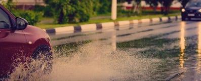 汽车飞溅水定调子的雨水坑 免版税图库摄影