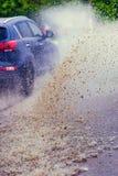 汽车飞溅水定调子的雨水坑 库存图片