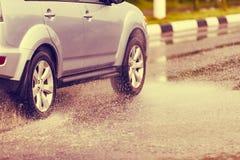 汽车飞溅水定调子的雨水坑 免版税库存图片