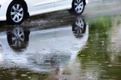 汽车飞溅水定调子的雨水坑 库存照片