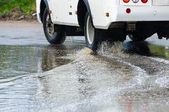 汽车飞溅水的雨水坑 库存图片
