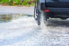 汽车飞溅水的雨水坑 图库摄影