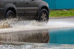 汽车飞溅水的雨水坑 免版税库存照片