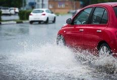 汽车飞溅水的雨水坑 免版税库存图片