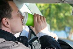 汽车饮料的司机从玻璃的一份精神充沛的饮料咖啡,特写镜头 库存照片