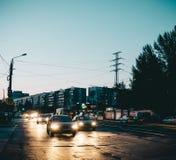 汽车,在沥青反映的光 议院,夜城市 翼果 免版税库存照片