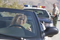汽车读书票的少妇 免版税库存图片