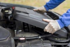 汽车维修车间 技工投入了塑料引擎盖子 库存照片
