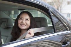汽车紧固安全带后座的少妇。 免版税库存图片
