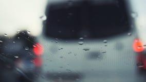 汽车玻璃在一个雨天- defocused背景 在挡风玻璃的刮水器的移动的waterdrops,水平 免版税图库摄影