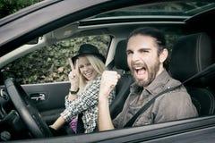 汽车-驾驶在新汽车尖叫的凉快的行家夫妇愉快,看照相机 免版税库存照片