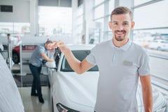 汽车deeler的图片在照相机站立并且看 他微笑并且把握汽车关键 潜在的采购员站立并且倾斜  免版税库存照片