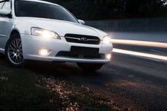 汽车Subaru在柏油路近的通过的汽车的遗产逗留在黄昏 免版税库存图片