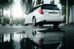 汽车Subaru遗产逗留在柏油路和反映在水坑在城市在白天 免版税库存照片