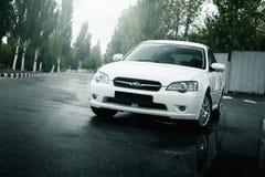 汽车Subaru遗产逗留在柏油路和反映在水坑在城市在白天 免版税图库摄影