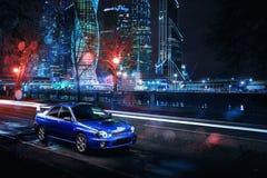汽车Subaru Impreza WRX立场在现代大厦附近的莫斯科市在晚上 库存照片