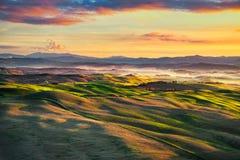 沃尔泰拉有雾的全景、绵延山和绿色领域在sunse 免版税库存图片