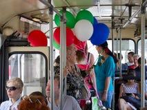 沃罗涅日,俄罗斯- 2013年6月07日,有气球的妇女在公共汽车上乘坐 库存图片